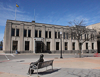 The MCC Downtown Center as view from across Third Street. A sculpture of Charles Hackley sitting on a bench is in the foreground.