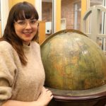 MCC student Stephanie Carr to compete in 2020 World GeoBowl. She poses next to the antique globe once housed in Hackley Library and now located in MCC's Hendrik Meijer Library.