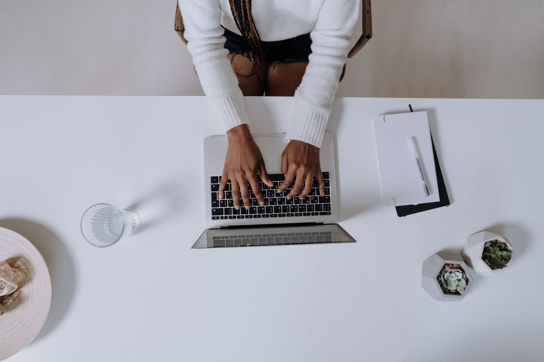 woman in white long sleeve shirt using macbook pro