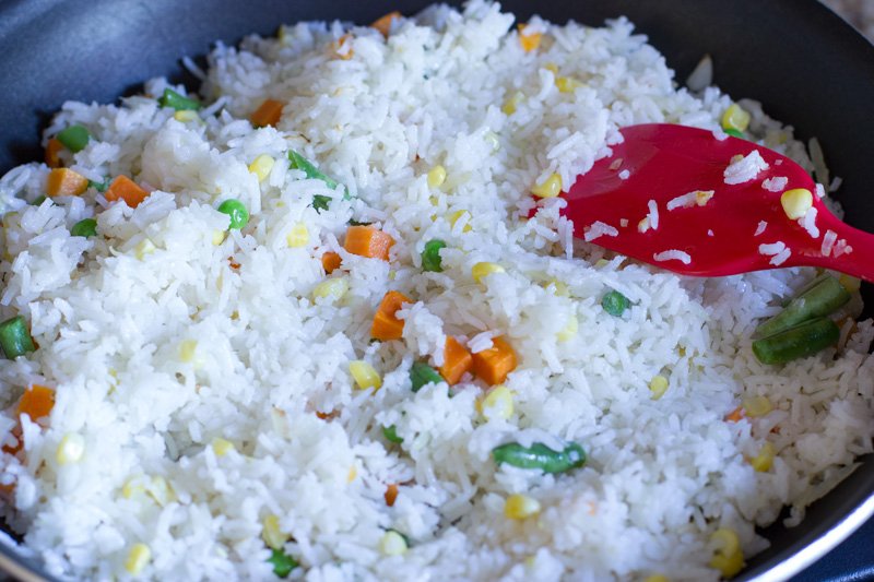 Stirring the veggies into the fried rice