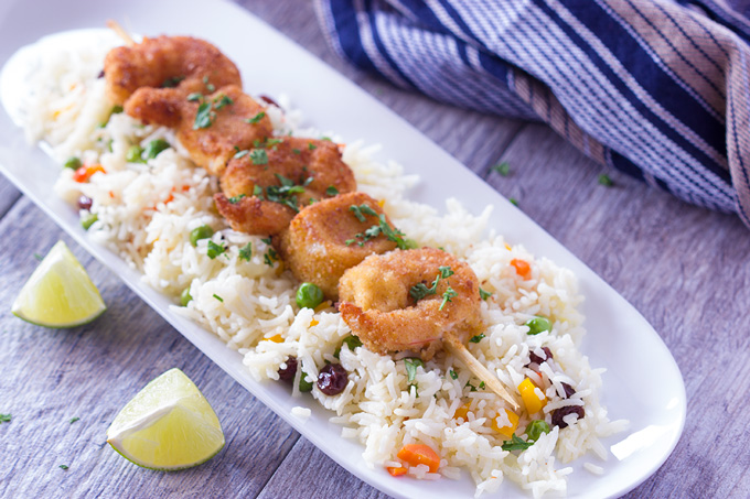 Greek shrimp skewers on a plate with rice