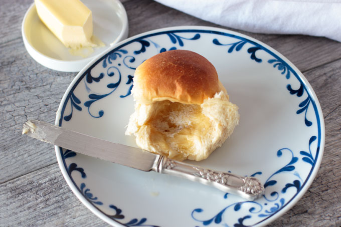 Sweet milk bread dinner roll on a plate with melted butter