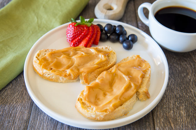 Two sliced of bread covered with milk caramel spread on a plate with fruit