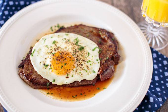 Steak and egg on a plate garnished with parsley, landscape orientation