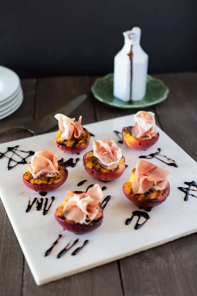 Grilled peaches with prosciutto on white marble with balsamic glaze