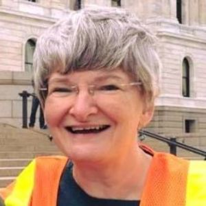 Karen Wills smiling at camera on steps of Minnesota State Capitol wearing a safety vest