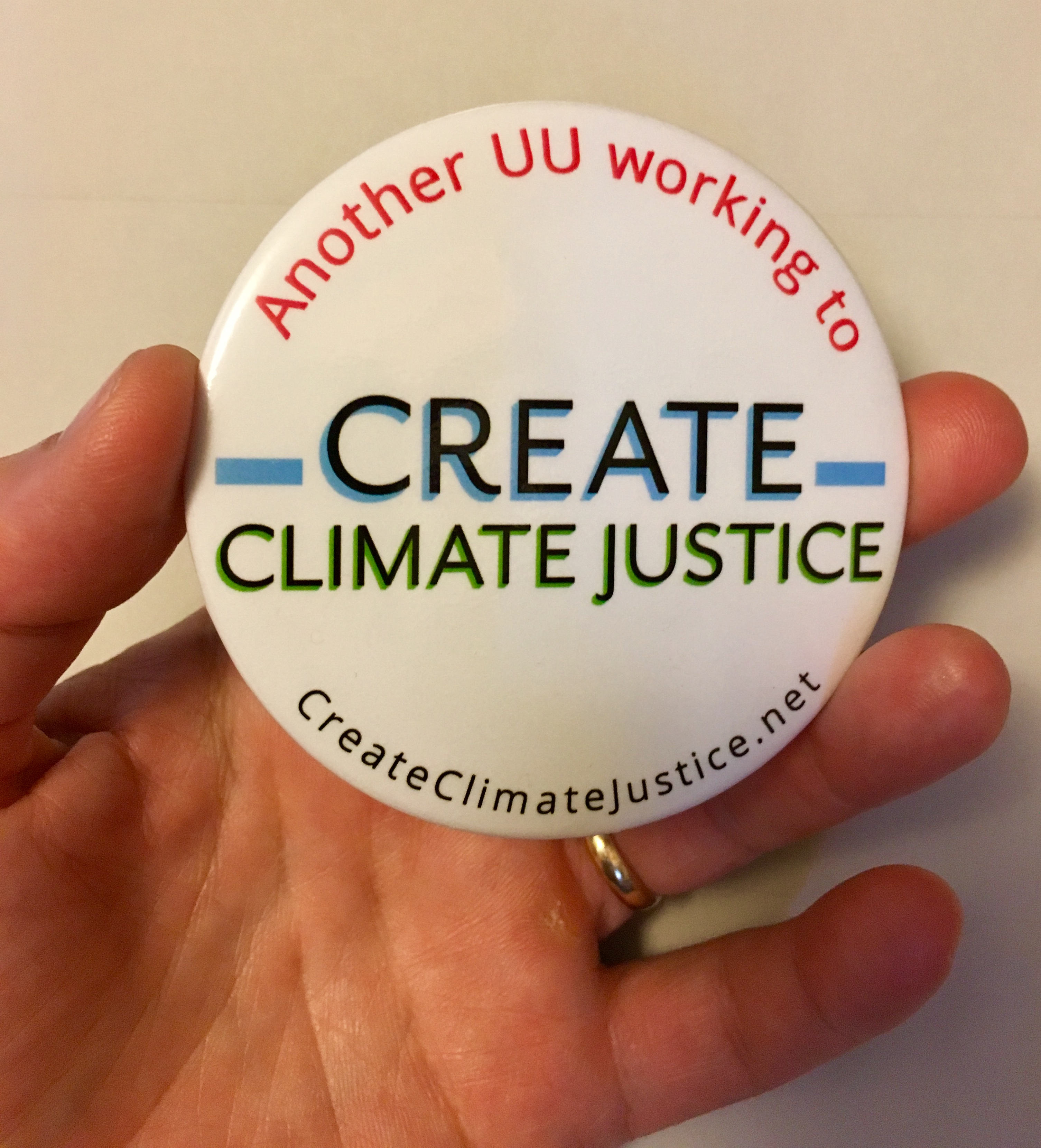 hand holding Create Climate Justice button