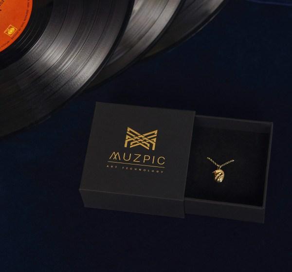 Imagen de regalo original, estuche de collar con joya de oro del compositor Bach sobre la obra Cello Suite.