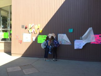 Students hang posters outside of the library.