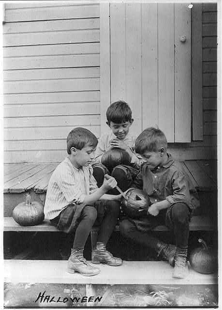 Three boys on porch steps cutting faces in pumpkins.