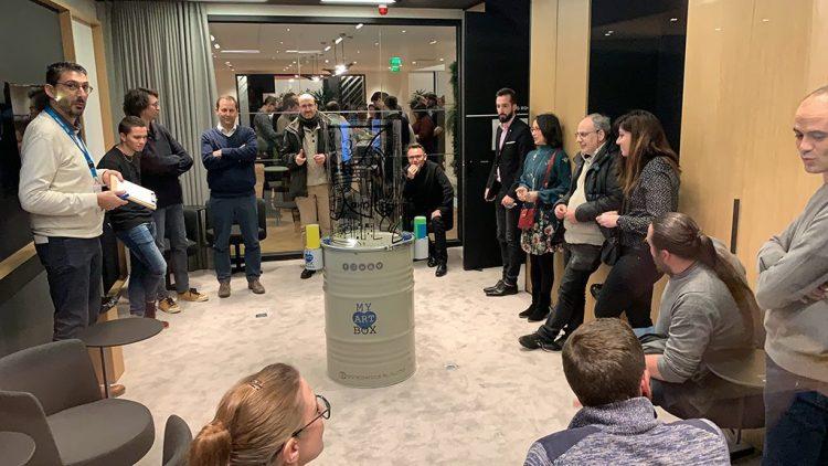 une art box Totem Box synergie composée d'une fresque tube cylindre transparent posée sur son bidon en acier de transport et de présentation, au milieu d'un groupe dans une salle de réunion de l'espace victoire à Paris