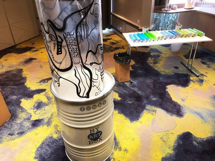 La Totem box Synergie est composée d'une fresque en cylindre transparent, d'un bidon industriel en acier de 200L et de tout le matériel adhésifs ciseaux corbeille de récupération des déchets