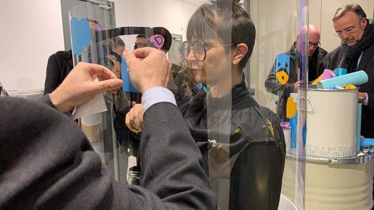 l'artiste aNa dans son tube totem plexi transparent avec un participant qui colle son autocollant en même temps