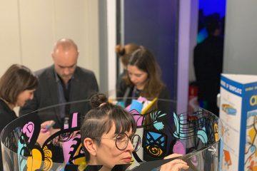 une artiste qui crée une oeuvre commune dans un tube transparent en même temps que les invités est une idée d'animation créative d'inauguration et pose de première pierre