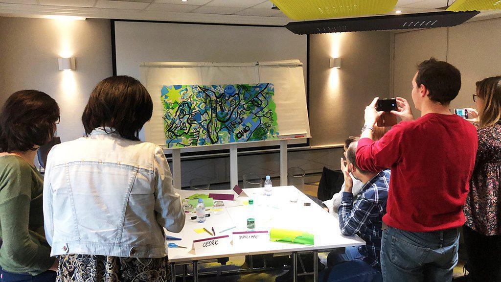 un groupe devant son oeuvre d'art réalisée lors d'un programme créatif de coaching aglilité