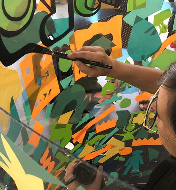 une artiste à lunettes rondes dessine à la ligne noire autour de formes de couleurs sur un support transparent plexi art en animation fresque géante lors d'un team building
