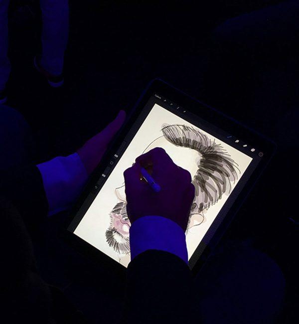 Photo d'un homme qui fait une caricature digitale en close up sur un iPad Pro