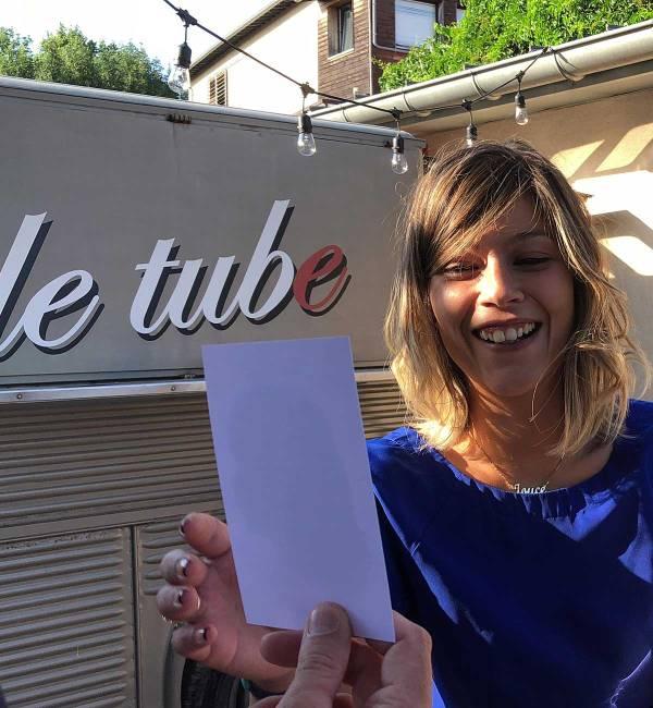 une jeune femme rit de plaisir en recevant son portrait silhouette réalisé lors d'une animation à Lyon durant un mariage