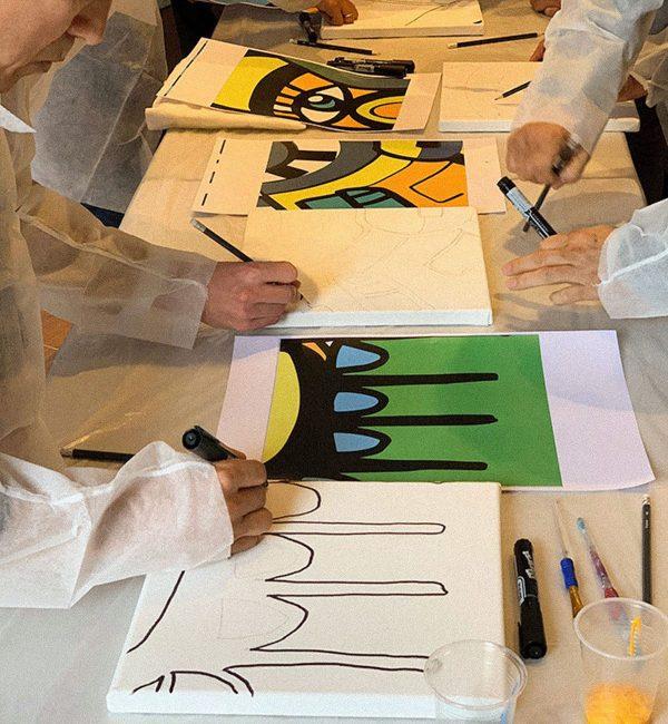 les collaborateurs dessine sur les toiles les visuels de l'artiste aNa