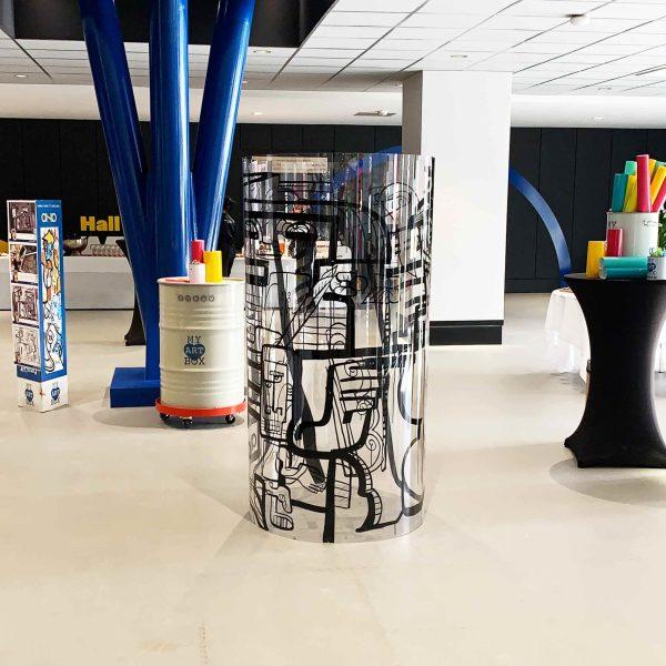 Un Tube Totem Plexi au centre de l'image avec tout le matériel d'animation fresque myartbox disposé autour.