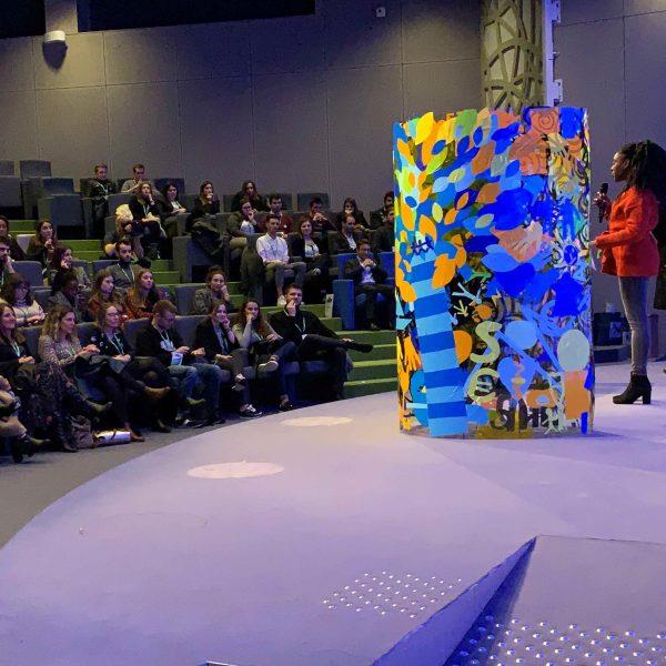 Une Fresque cylindre plexi Totem Animation fresque présentée sur scène par une jeune femme en veste rouge devant un publique ayant pris part à une animation séminaire original
