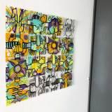 Un tableau DIY Happiness management my art box composé de 16 plaques plexi personnalisée avec des couleurs vives et posé sur un mur blanc à coté d'un mur gris