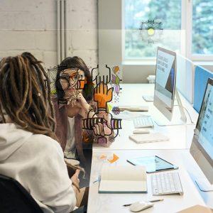 team building plexi entre deux femmes au bureau qui décore la paroi de séparation entre leurs postes de travail
