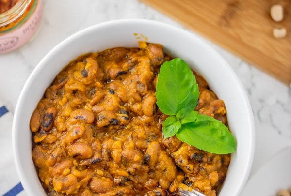 stewed beans in a bowl with a garnish of basil leaves.