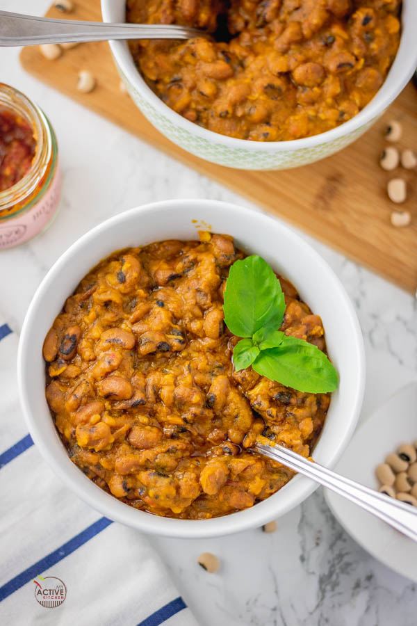 Nigerian stewed beans in a bowl (ewa riro) with a garnish of basil leaves.