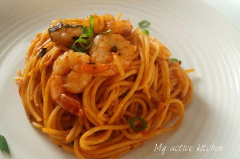 a close shot of jollof spagheti with prawns and uziza