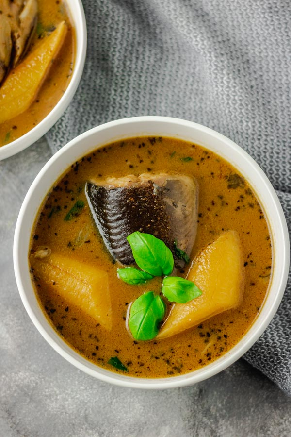 catfish pepper soup with plantain garnised with fresh basil.