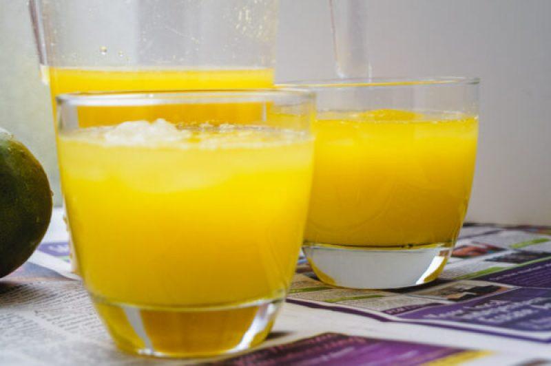 two glasses of mango lemonade on a table
