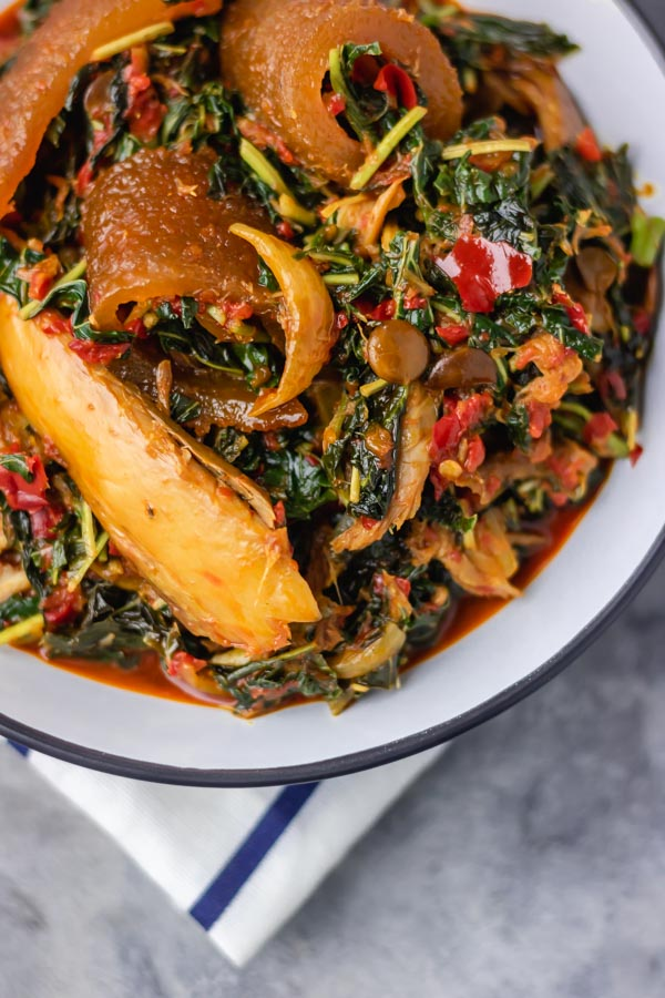 a bowl of efo riro loaded with ponmo and smoked mackerel.