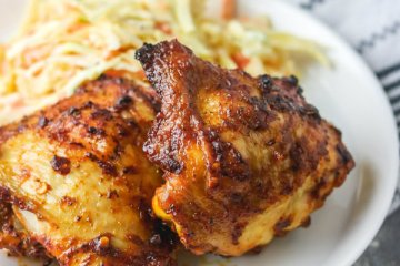 baked spicy chicken thigh on a plate with coleslaw