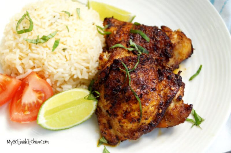 spiced chicken served with rice and a side of lime and tomatoes