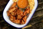 crispy fried chicken wings and chips in a pan.