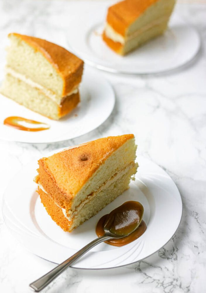 vanilla sponge cake on a plate with caramel and spoon