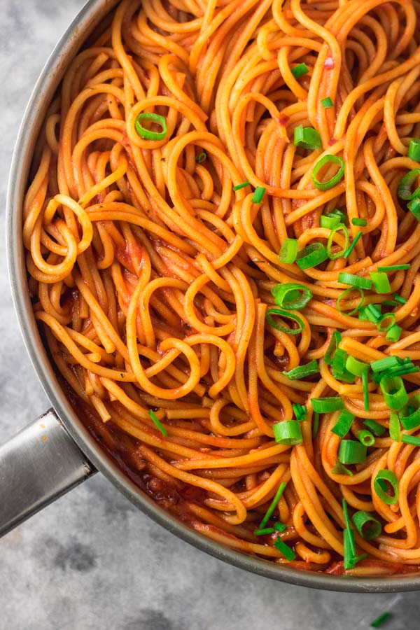 cooked pasta in pan, a black thong is placed on the pasta. the pasta is garnished with chopped pasta and chive