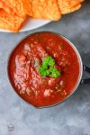 overhead shout of homemade blender salsa in a small serving saucepan and a side of corn chips.