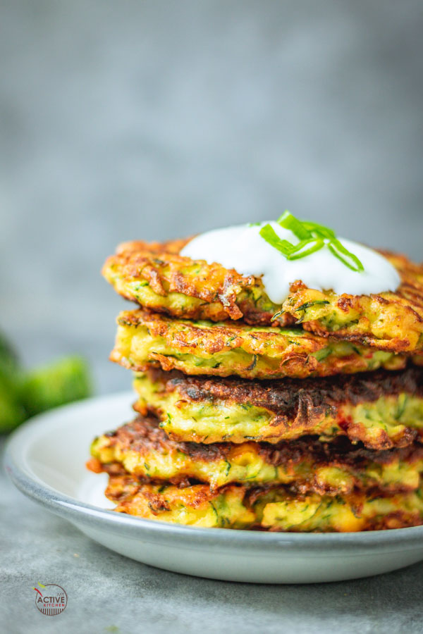 stack of crispy courgette and sweetcorn fritters with a dollop of yogurt and spring onions on a plate.