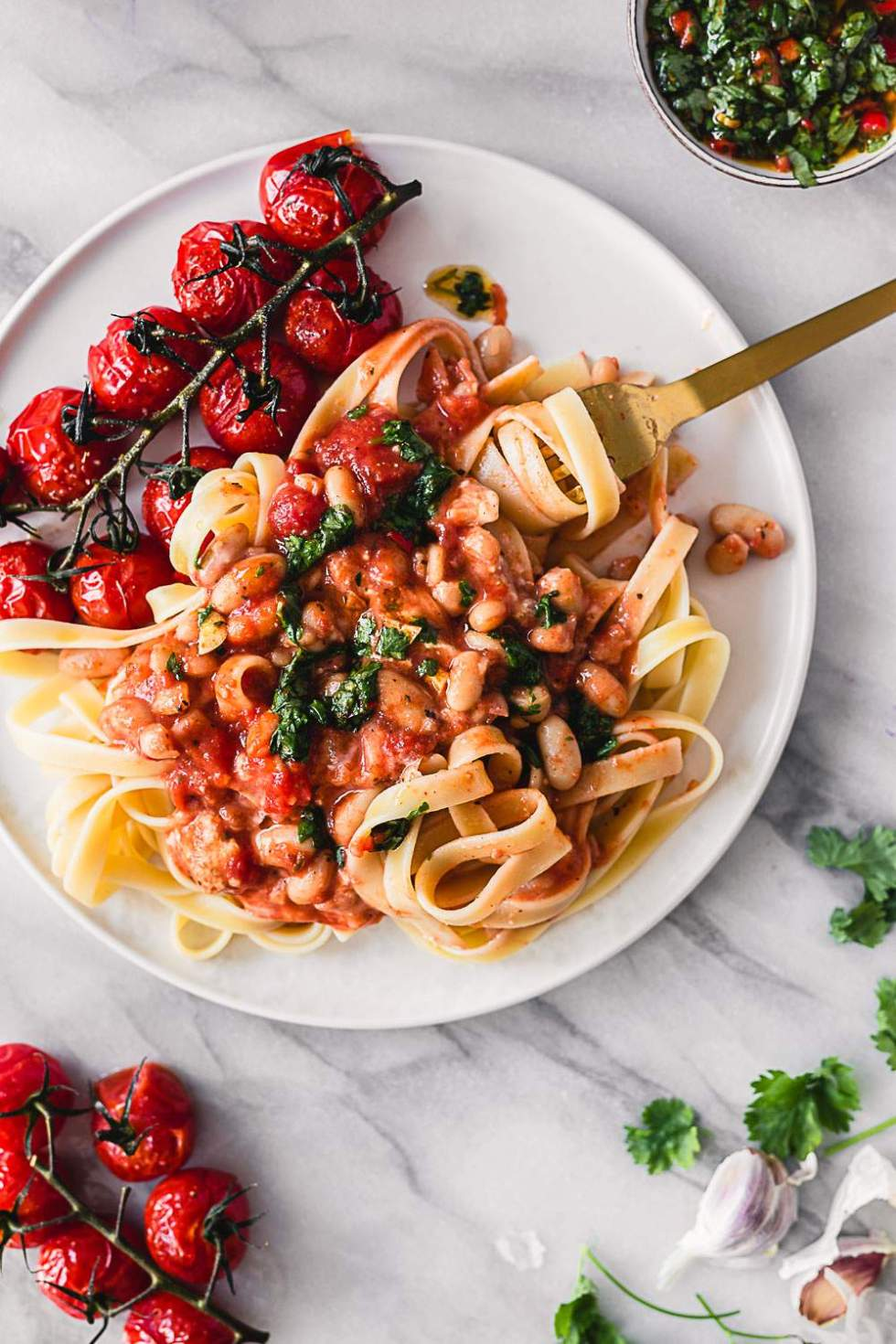 Tomato baked white beans with vegan feta and chimichurri