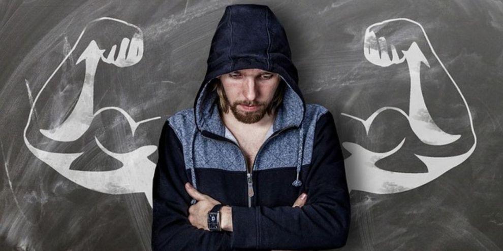 Man leaning on chalkboard looking down with flexed biceps drawn on chalkboard