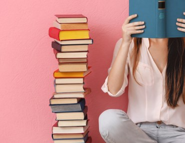 Girl reading a book beside a tall pile of books with a pink wall