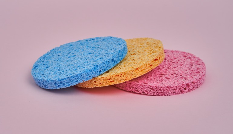 Three flat round sponges (blue, yellow, pink) stacked on top of each other with a pink background