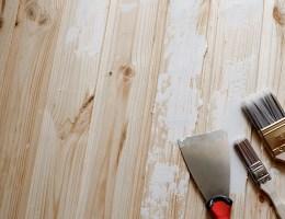 Spatula, putty paste, brush on a peeling wooden wall