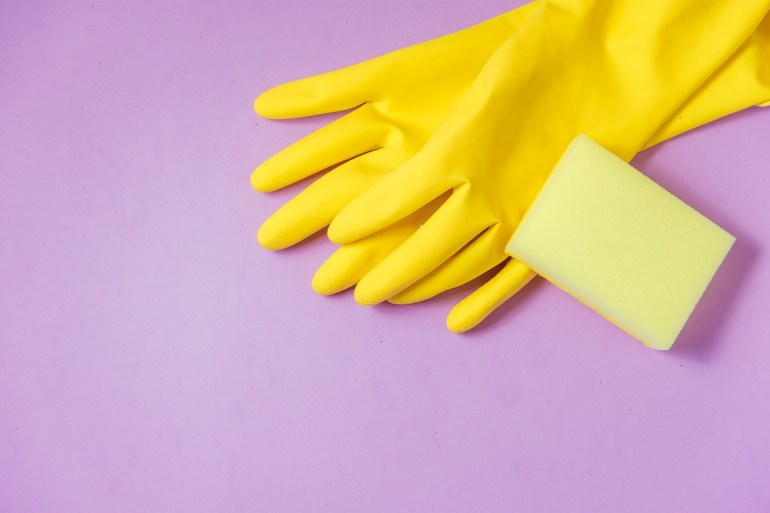 Yellow gloves and a yellow sponge on top of a purple background
