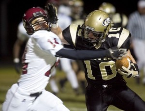Woodland's Jack DeBiase delivers a stiff arm to Torrington's Garrett Perusse during the Hawks' 34-12 win on Friday.