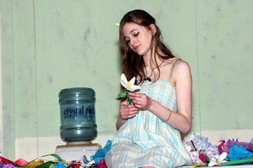 Freshman Haley Diaz makes paper flowers in her role as Ophelia during rehearsal for the school play last week.