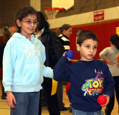 Paulo Adrantes, 4, and Elaine Adrantes, 9 compete to throw a ball into the catchers mitt for points.