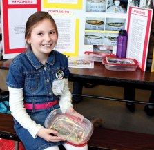 """Giulianna Pinevich, 8, shows off her mummified fish. She found that a mixture of salt, baking soda and borax mummify fish the best. Pinevich said her parents are glad the experiment is over. """"My whole kitchen was smelly,"""" she said."""